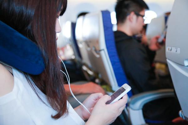 飞机上使用3c产品,飞机上滑手机,飞机上玩手机,飞机上听音乐,戴耳机(图/记者林世文摄)